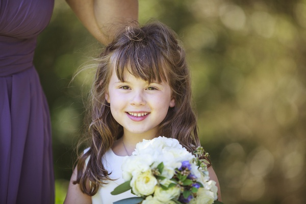 Flower girl in white sleveless dress carries bridesmaid's bouquet of white and purple flowers