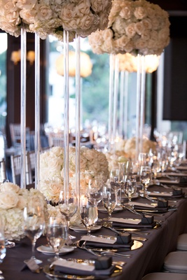 Wedding reception long table dark grey linen tall lucite acrylic riser white flowers low flowers