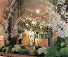 White and green flowers, branches, and greenery decorate a wedding reception