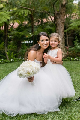 Bride in strapless Monique Lhuillier wedding dress with peony bouquet and flower girl dress