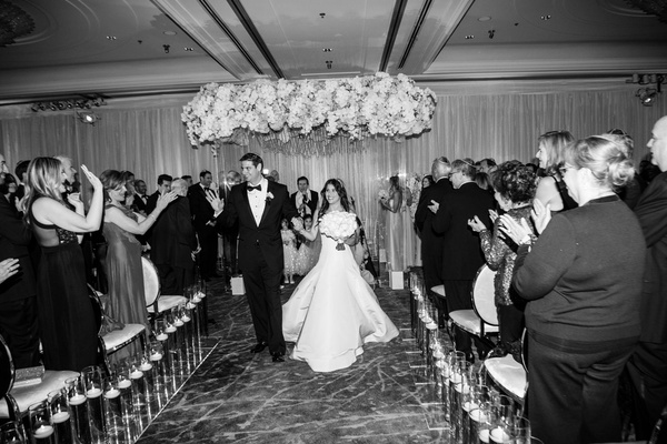 Black and white photo of bride and groom husband wife recessional walking up carpet aisle candles