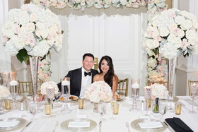 bride groom smiling white head table tall floral centerpieces pink white green vases floral arch