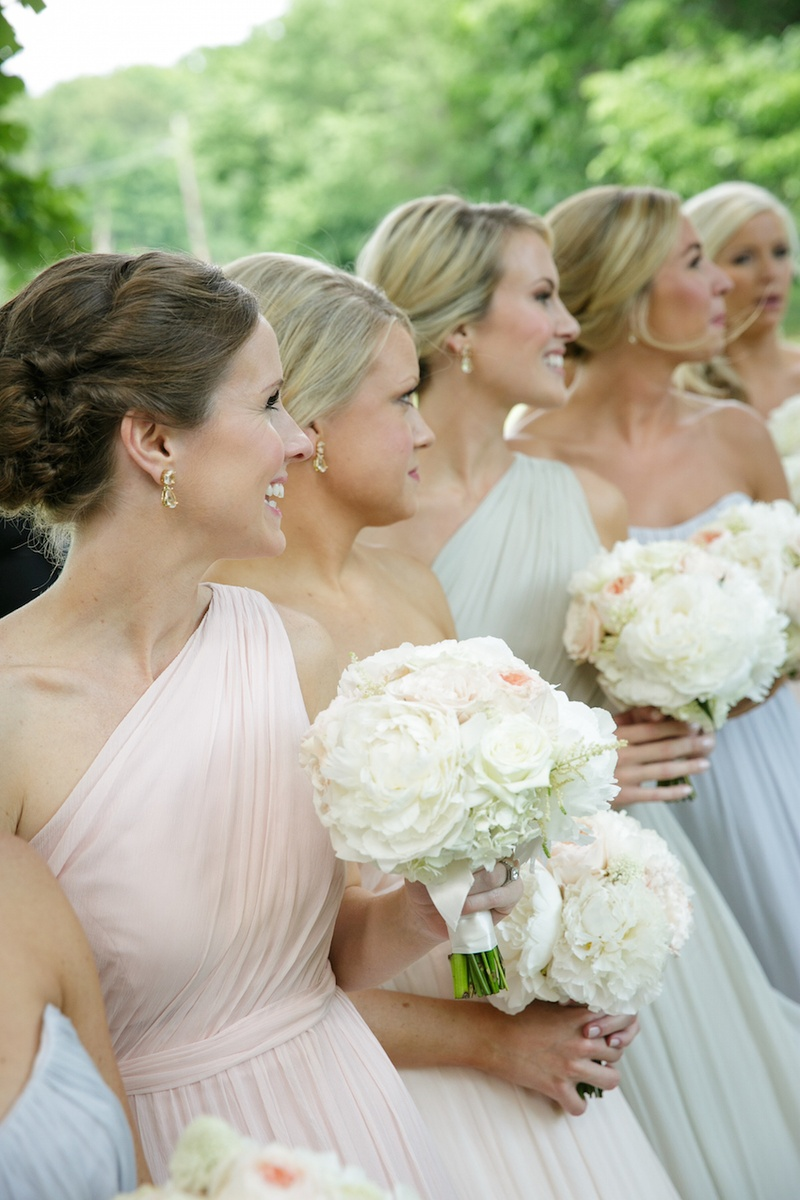 Bridesmaids in strapless and one-shoulder gowns in pastel shades