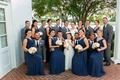 Bride, groom in grey suit, groomsmen in grey suits navy ties, bridesmaids in long navy dresses