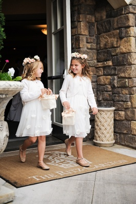Two flower girls in white dresses, cardigans, and flower crowns