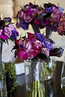 Purple orchid and rose bouquets in glass vases