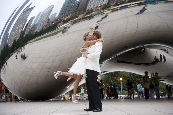Bride in short dress kisses groom in tuxedo of white coat and black pants in Millennium Park