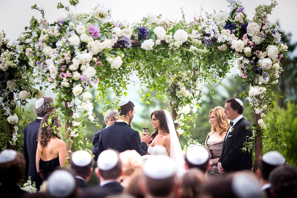 outdoor jewish wedding ceremony yarmulke on guests flower chuppah outdoor ceremony purple white pink