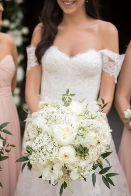 bride in lace off shoulder gown holding white rose astilbe sweet pea and ranunculus flowers