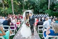 bride in alfred angelo gown, groom in dark navy grey suit sit kiss at end of aisle