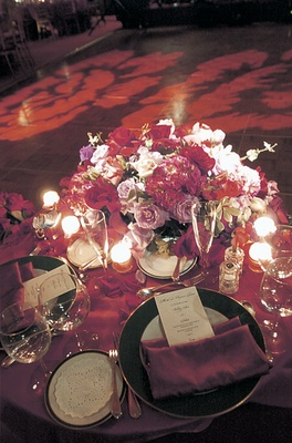 Wedding reception table with red tablecloth and napkins and bouquet of roses