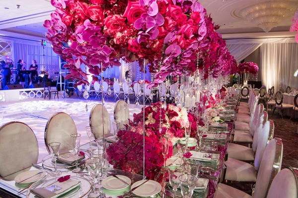 Velvet and chrome oval chairs mirror table acrylic stand pink orchid rose centerpiece flowers under