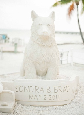 Cocktail hour wedding on sand beach sand sculpture of dog