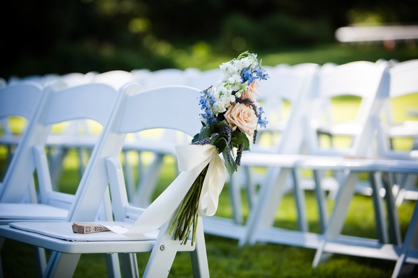white folding chairs with bouquet tied on end
