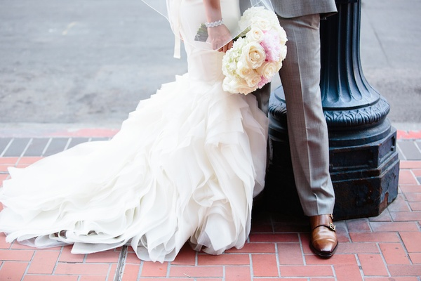 Bride in a Vera Wang dress with ruffled skirt and groom in grey suit with brown shoes