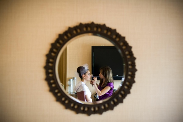 Bride and makeup artist in mirror