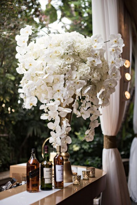 Outdoor bar area for cocktail hour gold riser white orchid rose hydrangea flowers alcohol candles