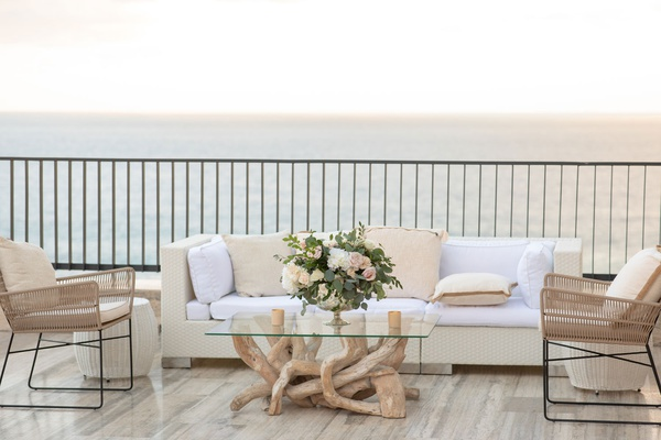 wedding reception lounge area driftwood coffee table vase with eucalyptus leaves flowers white pink