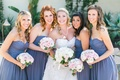 Bride in Oscar de la Renta strapless wedding dress with bridesmaids in strapless purple dresses