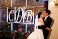 Bride and groom kiss in front of ice sculpture wall
