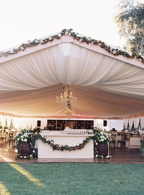Wedding reception bar with magnolia leaf garland in tent draping chandeliers string lights