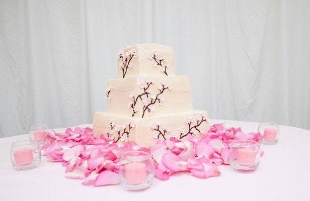 Wedding cake on pink rose petals with cherry blossom design