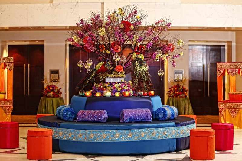 Round couch in royal blue with blue and purple cushions is topped with candles and color flowers
