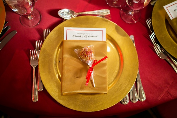 red and gold cake pop placed on gold place setting red linen at wedding reception