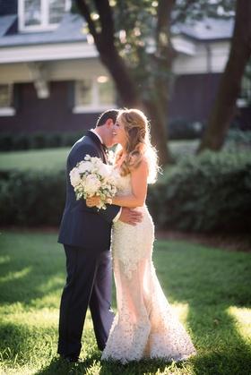 bride in zuhair murad laughs while groom in j. hilburn whispers in ear