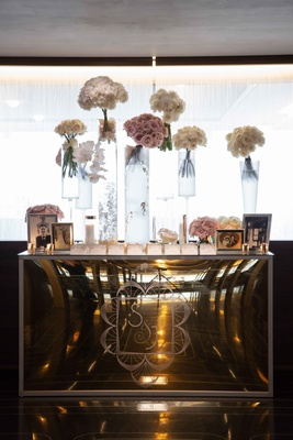 Mirror escort card table with tall glass vases topped with bouquets of white and pink flowers frames