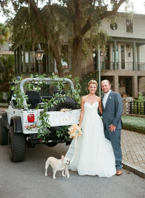 Bride in strapless wedding dress with groom in grey suit jeep wrangler french bull dog greenery