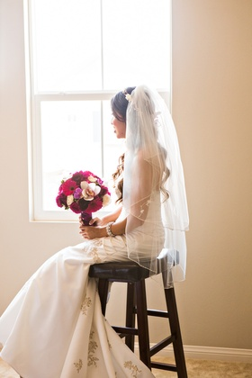 Bride sitting at window in veil from David's Bridal