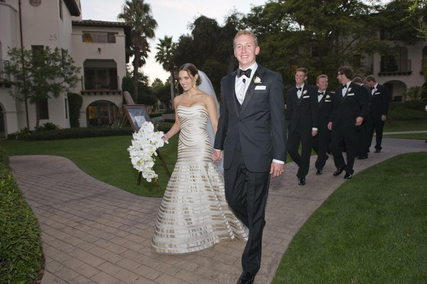 Bride in a strapless Vera Wang gown walks with groom and groomsmen to reception