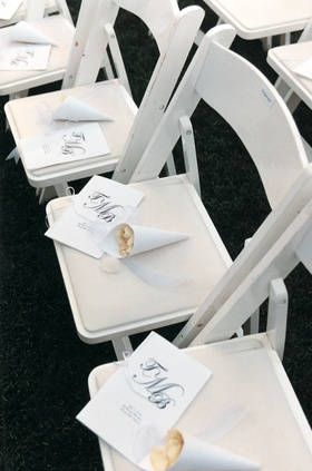 Monogrammed program on white chairs