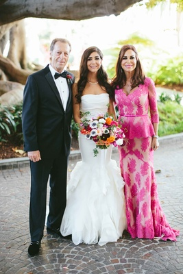 classic suit, mother of bride pink peplum gown with quarter-sleeves, bride with parents