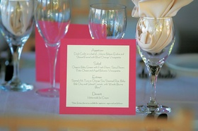 Pink and white menus on wine glass table