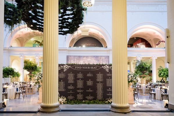 museum wedding reception the field museum tall columns and black white seating chart greenery decor