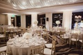 Wedding reception ballroom neutral colors white flowers gold chairs crystals on ceiling