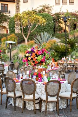 outdoor wedding reception bohemian chic rikki ladenheim events wood chair pink orange yellow purple