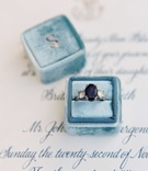 Light blue velvet Mrs. box with three stone heirloom diamond ring with blue oval sapphire center