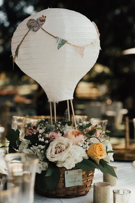 paper lantern wedding centerpiece designed to look like a hot air balloon with basket of flowers