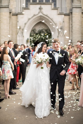 bride in lace trim veil and groom walking out of church flower petal toss before walking reception