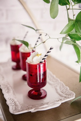 Wedding reception drinks, black and white straw, whipped cream, golden sugar in small red glasses