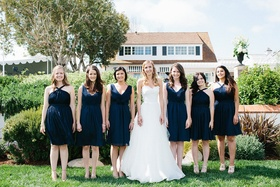 Bride in white wedding dress with bridesmaids in short navy blue bridesmaid dresses