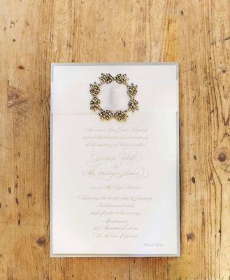 Winter wedding invitation with metallic script, white ribbon, and wreath brooch detail