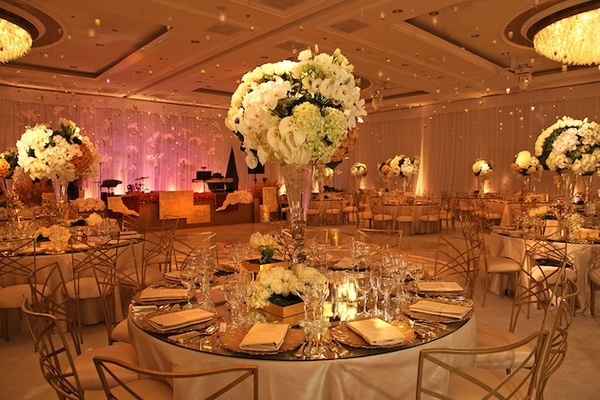Round reception tables with mirror tops and ivory centerpieces