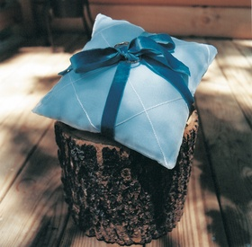 Blue wedding ring pillow with ribbon on tree trunk