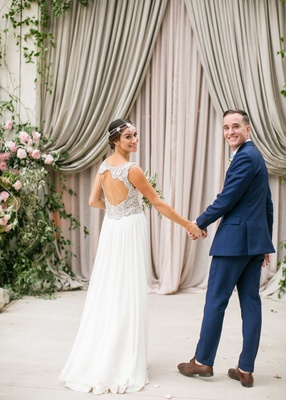 Bride in keyhole back Jenny Packham wedding dress groom in navy blue suit in front of barn drapery