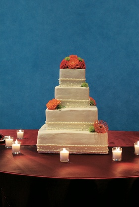 Four layer white cake with pearl decorations and green and orange flowers