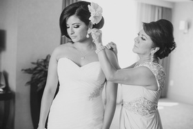 Black and white photo of mother adding earrings to bride